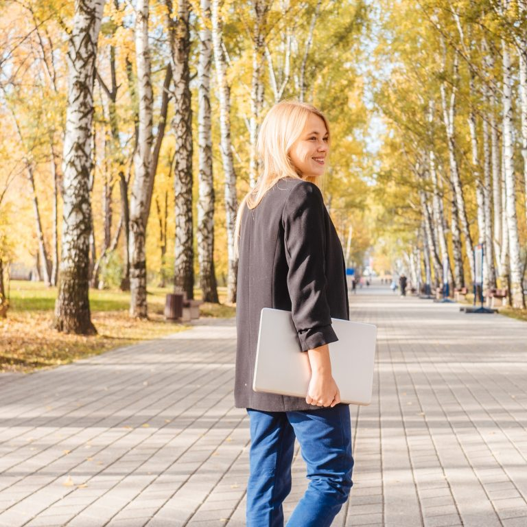Young woman hold laptop in park